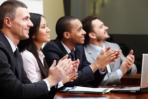 Multi ethnic business group greets somebody with clapping and smiling. Focus on woman.jpeg