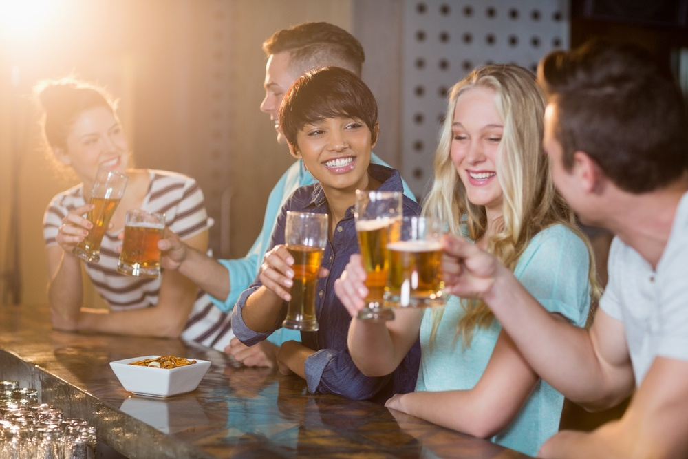 Group of smiling friends toasting glass of beer at counter in bar.jpeg