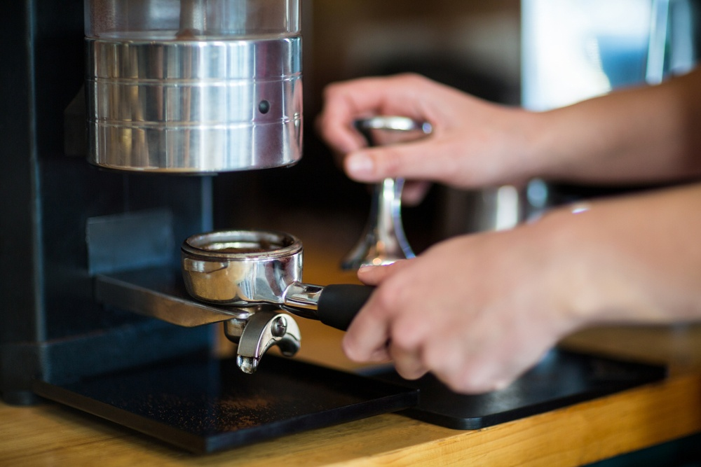 Waiter using a tamper to press ground coffee into a portafilter in cafx92xA9.jpeg