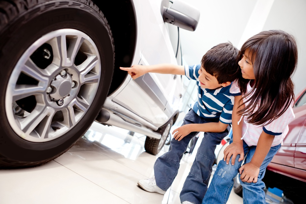 Kids in the dealer looking at car wheels.jpeg