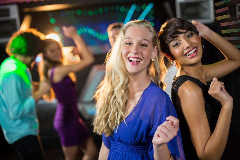 Two beautiful women dancing on dance floor in bar.jpeg