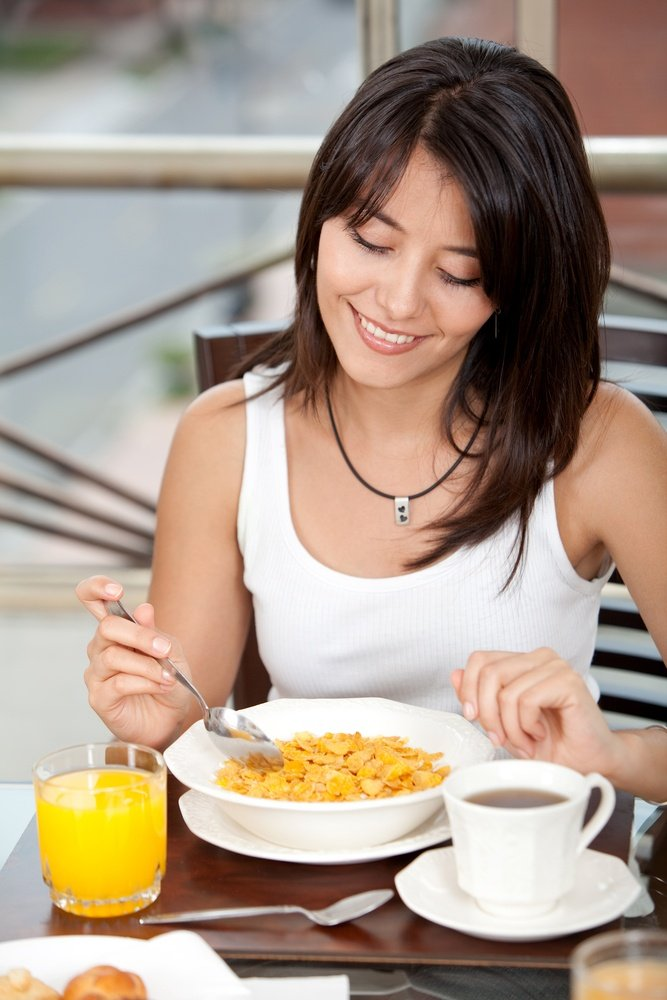 Beautiful woman eating her breakfast at home.jpeg