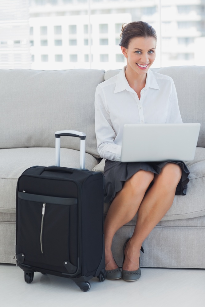 Businesswoman sitting on the couch with laptop with suitcase.jpeg