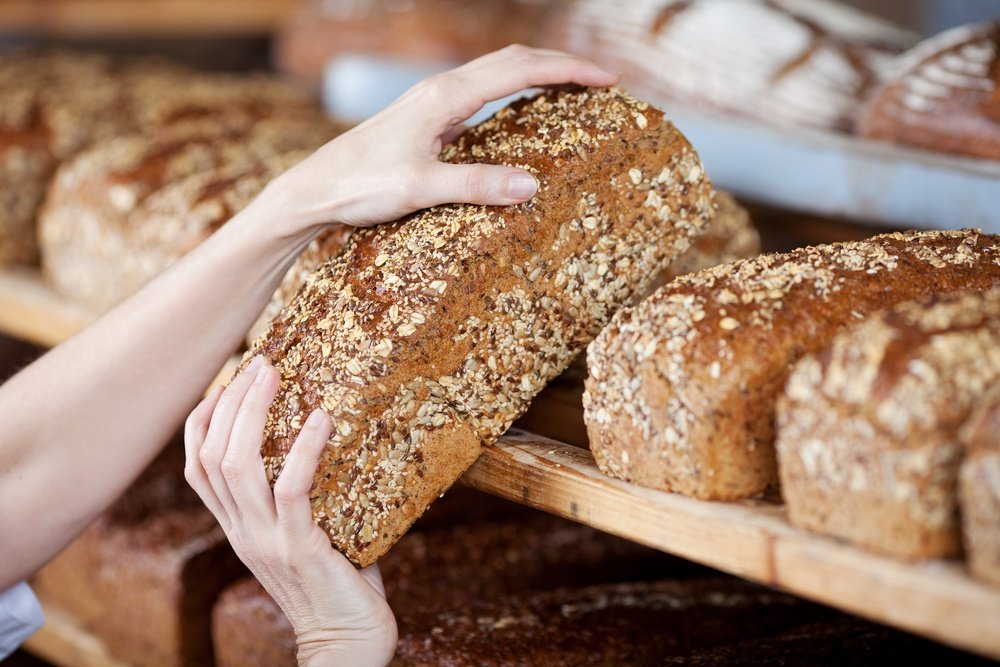 Cropped image of female bakery worker's hands removing whole grain bread loaf from shelves.jpeg