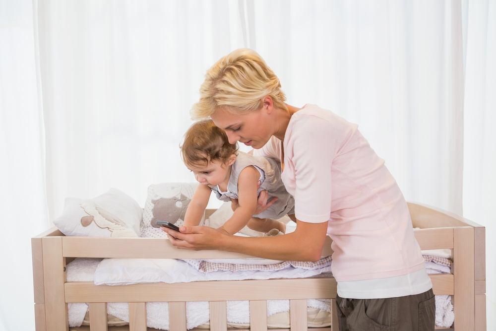 Happy blonde woman with his son using phone at home in bedroom.jpeg