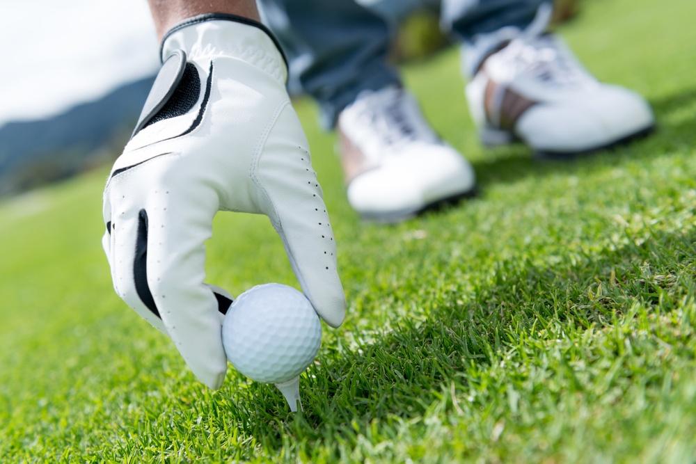 Man placing golf ball at the tee box .jpeg