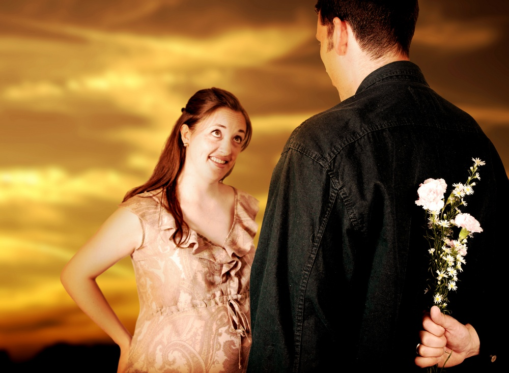 couple at sunset - guy hiding flowers - focus on flowers.jpeg