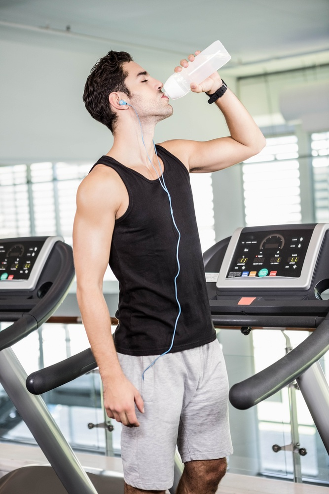 handsome man on treadmill drinking water at the gym.jpeg